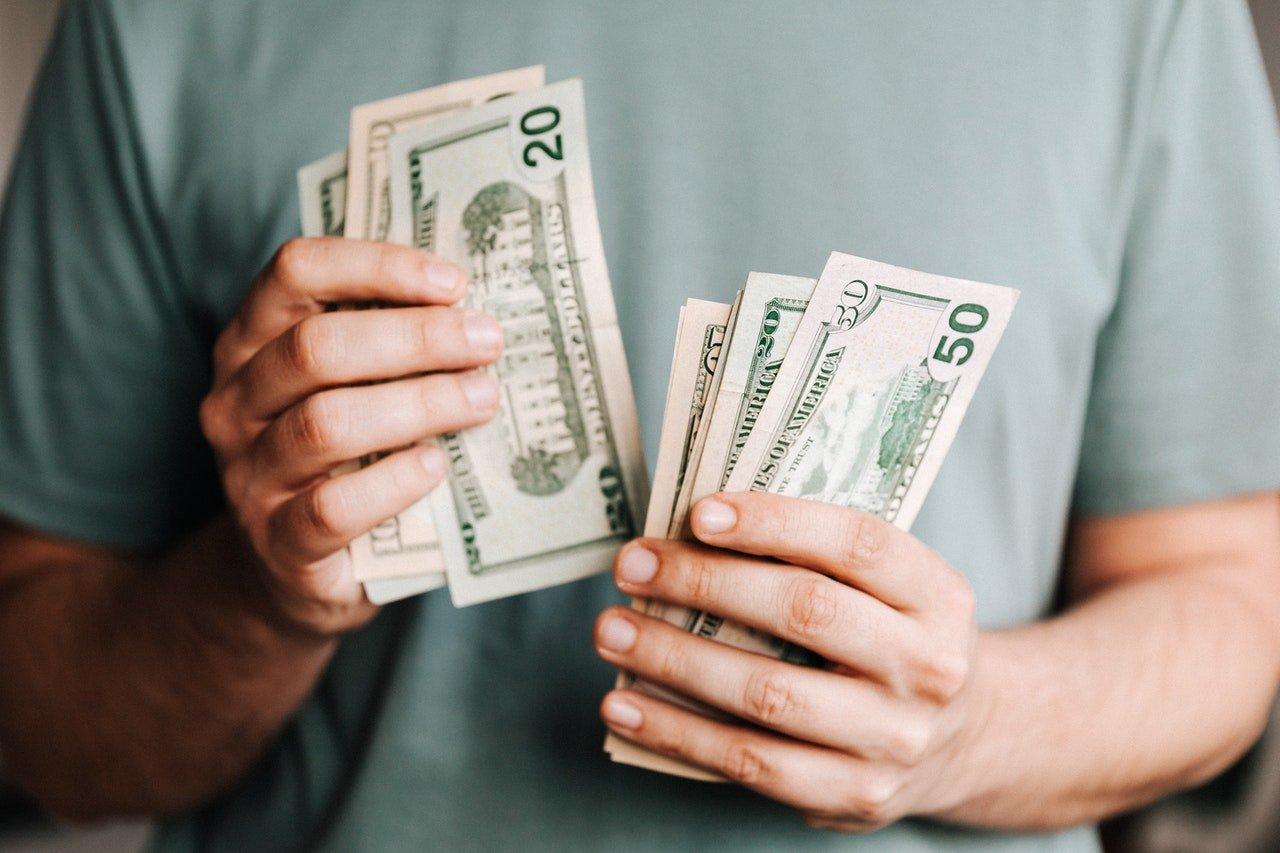 crop-man-counting-dollar-banknotes-4386431